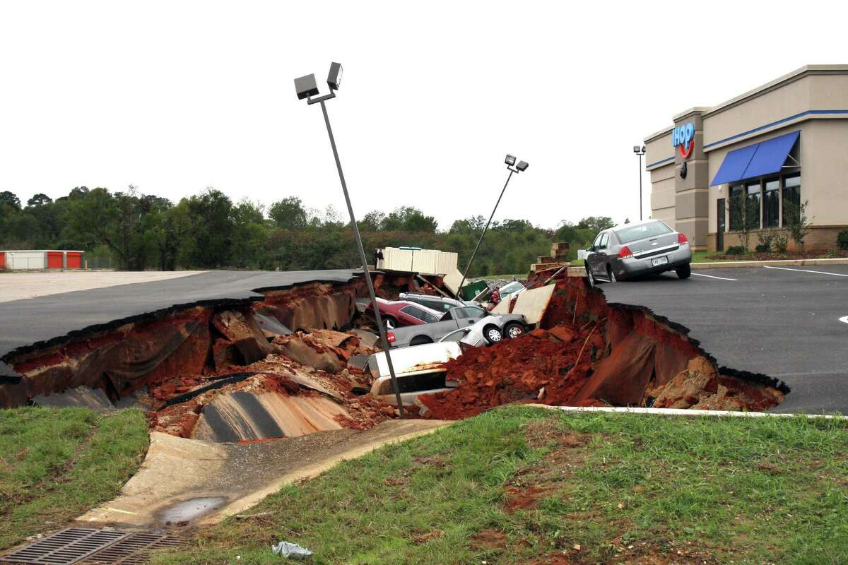A sedan rests precariously on the edge of a collapsed section of parking lot at an IHOP in in Meridian, Miss. No injuries were reported in the collapse.