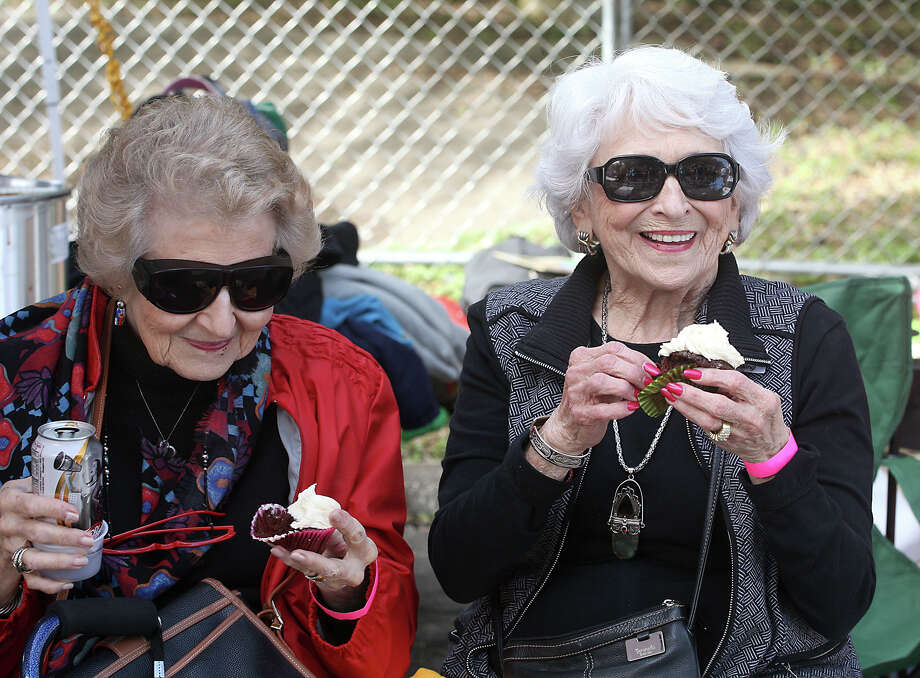 Glenda Alter (left) and Idelle Abramson enjoy an kosher cupcake as they watch people go by during the third annual Texas Kosher BBQ Championship Sunday, Nov. 8, 2015 at the Congregation Agudas Achim with proceeds benefiting the Fisher House. The women said the cupcakes were good and the salmon at the event was wonderful.  This year there were 19 BBQ teams, both Jewish and non Jewish, to participate in the event from all over the state and the winner of the People's Choice award will have money donated to the charity of their choice. Every team had four items for sampling including salmon, brisket, chicken and beans which the cooking and food was overseen by Rabbi Jeffery Abraham. H-E-B sponsors the event and provides the Kosher food for the event, which is said to take a year to accumulate, according to Robi Jalnos, chairman of the event. Photo: Cynthia Esparza, For The Express-News / For The San Antonio Express-News / For the San Antonio Express-News