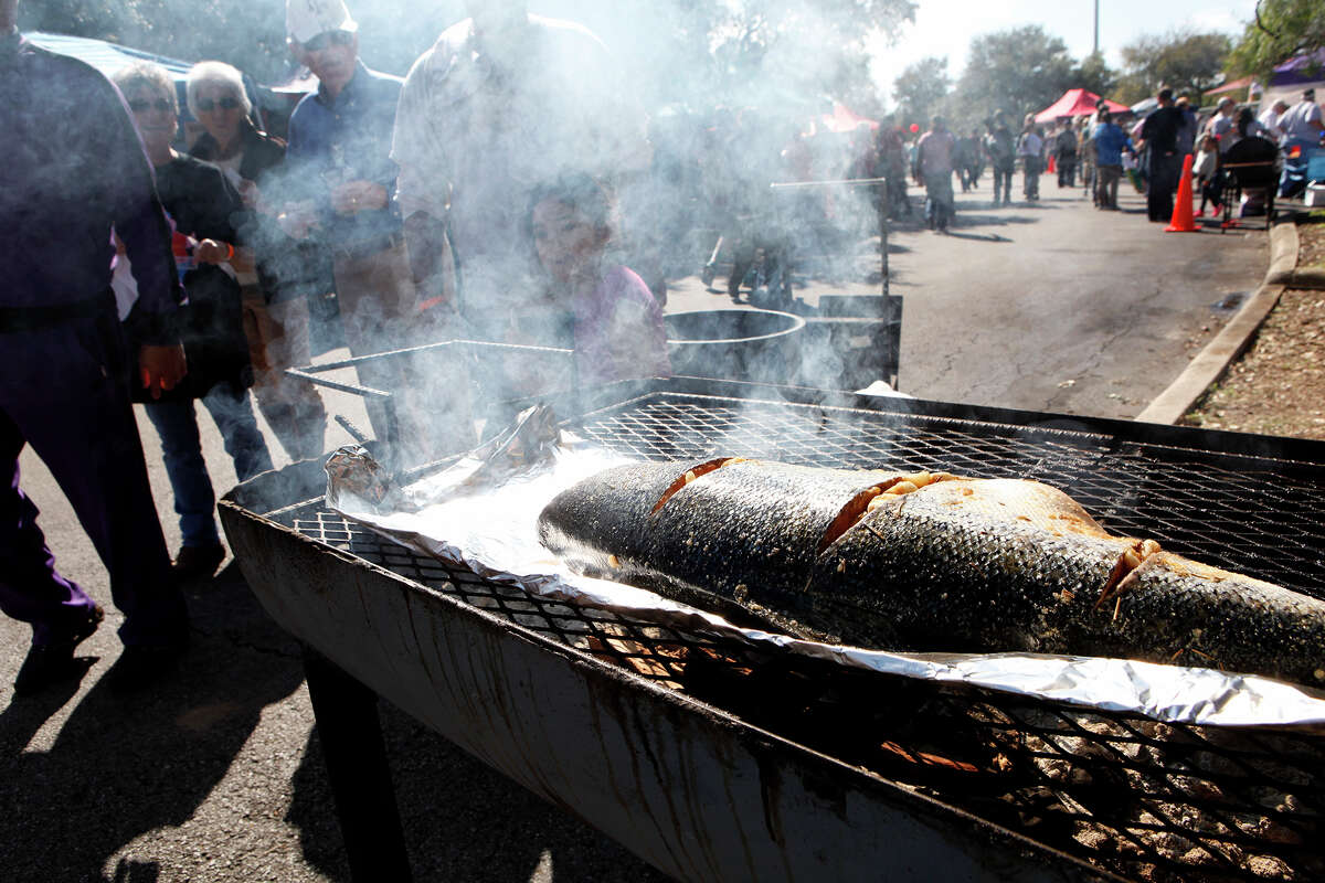 People pass by a salmon cooking at the Texas Kosher BBQ Championship Sunday, Nov. 8, 2015 at the Congregation Agudas Achim with proceeds benefiting the Fisher House. This year there were 19 BBQ teams, both Jewish and non Jewish, to participate in the event from all over the state and the winner of the People's Choice award will have money donated to the charity of their choice. Every team had four items for sampling including salmon, brisket, chicken and beans which the cooking and food was overseen by Rabbi Jeffery Abraham. H-E-B sponsors the event and provides the Kosher food for the event, which is said to take a year to accumulate, according to Robi Jalnos, chairman of the event.