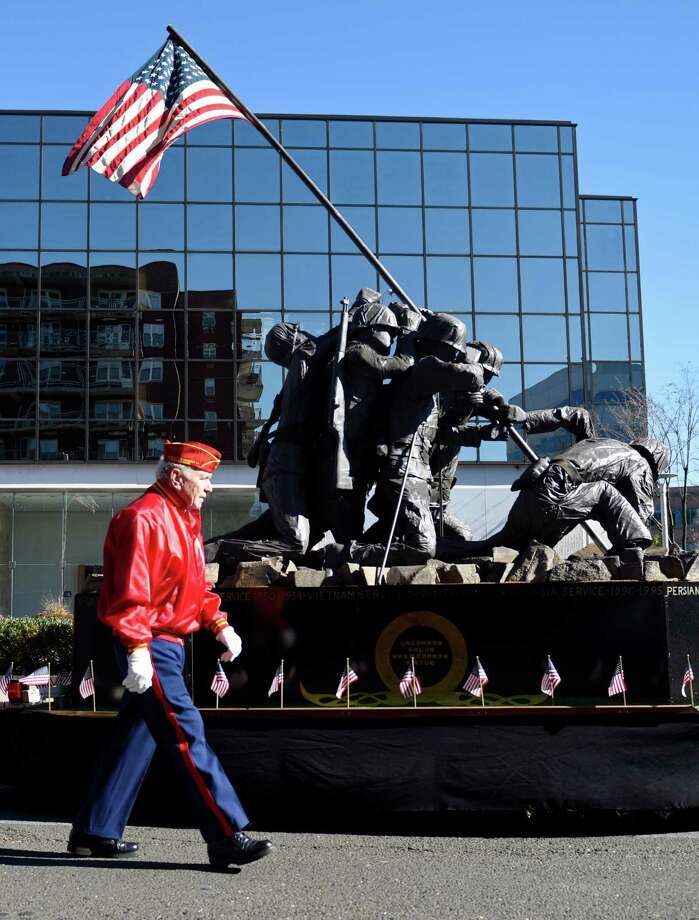 Stamford's Bill McGirr, who served in the U.S. Marine Corps from 1947-1952, marches beside a statue of the flag-raising on Iwo Jima at the 2015 Veteran's Day Parade in downtown Stamford, Conn. Sunday, Nov. 8, 2015.  U.S. Army veteran Dan Santagata, 91, was this year's grand marshal in the parade, which included participation from local police and fire departments, schools and veterans young and old. Photo: Tyler Sizemore / Hearst Connecticut Media / Greenwich Time