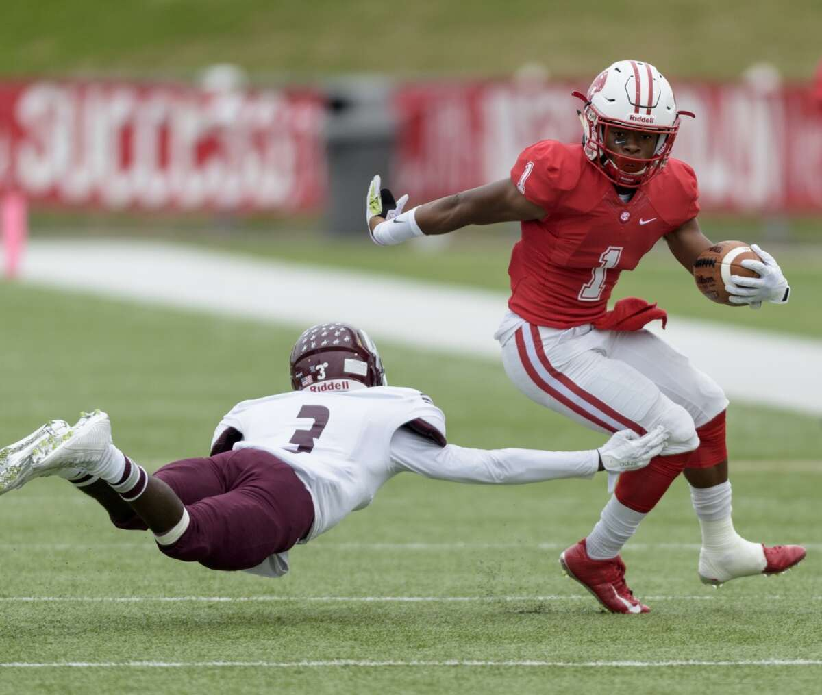 Tony Mullins (1) of the Katy Tigers breaks the tackle of Reggie Tati (3) of the Cinco Ranch Cougars in the first half of a high school football game on Saturday, November 7, 2015 at Rhodes Stadium.
