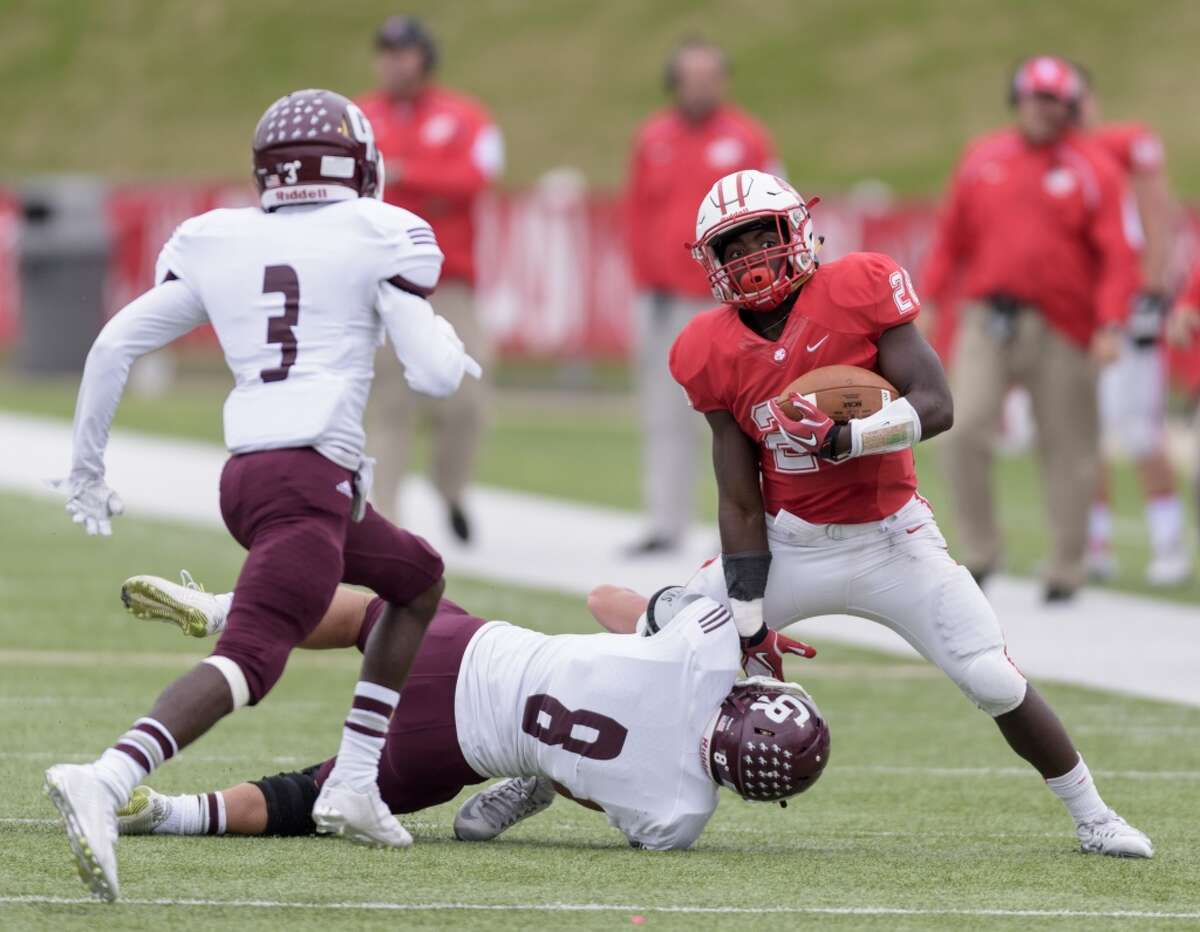 Kadarius Page (28) of the Katy Tigers is brought down by Ben Mathiasmeier (8) of the Cinco Ranch Cougars in the first half in a high school football game on Saturday, November 7, 2015 at Rhodes Stadium.