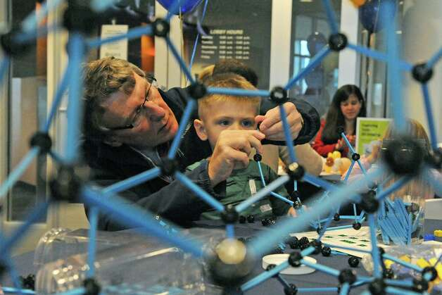 Al Lawrence of Albany works with his grandson two-year-old Zachary McAllister building a construction during SUNY Polytechnic Institute's Colleges of Nanoscale Science and Engineering family day on Saturday Nov. 7, 2015 in Albany, N.Y.  (Michael P. Farrell/Times Union) Photo: Michael P. Farrell / 00034122A