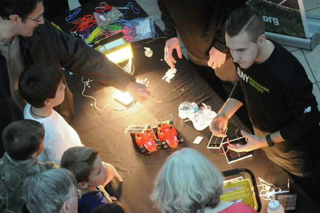 Graduate student Shane McMahon, right, explains renewable energy technology during SUNY Polytechnic Institute's Colleges of Nanoscale Science and Engineering family day on Saturday Nov. 7, 2015 in Albany, N.Y.  (Michael P. Farrell/Times Union) Photo: Michael P. Farrell / 00034122A