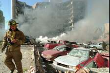 FILE - In this April 19, 1995 file photo, an Oklahoma City fireman walks near explosion-damaged cars on the north side of the Alfred Murrah Federal Building in Oklahoma City after a car bomb blast. More than 600 people were injured in the attack and 168 people were killed. Timothy McVeigh was executed in 2001 and Terry Nichols is serving multiple life sentences on federal and state convictions for their convictions in the bombing. (AP Photo/The Daily Oklahoman, Jim Argo, File) MANDATORY CREDIT