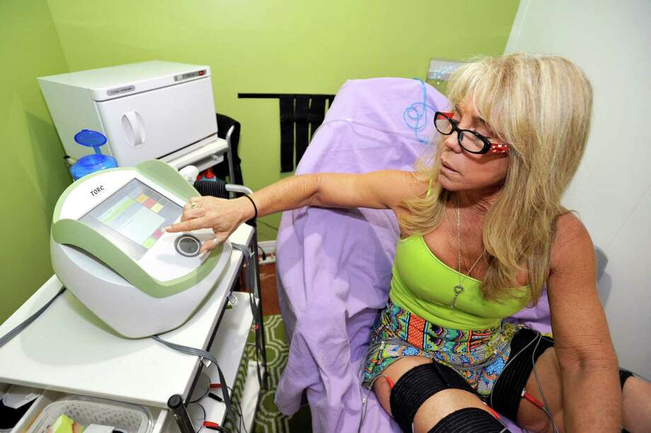 Tracey Scalzi, owner of 7e Fit Spa in Stamford, adjusts the intensity of the torc pads on her thighs on Thursday, Oct. 22, 2015. Torc treatments are small, electrical stimuli meant to tone muscles and are applied for 30 minutes to a target area. Photo: Michael Cummo / Hearst Connecticut Media / Stamford Advocate