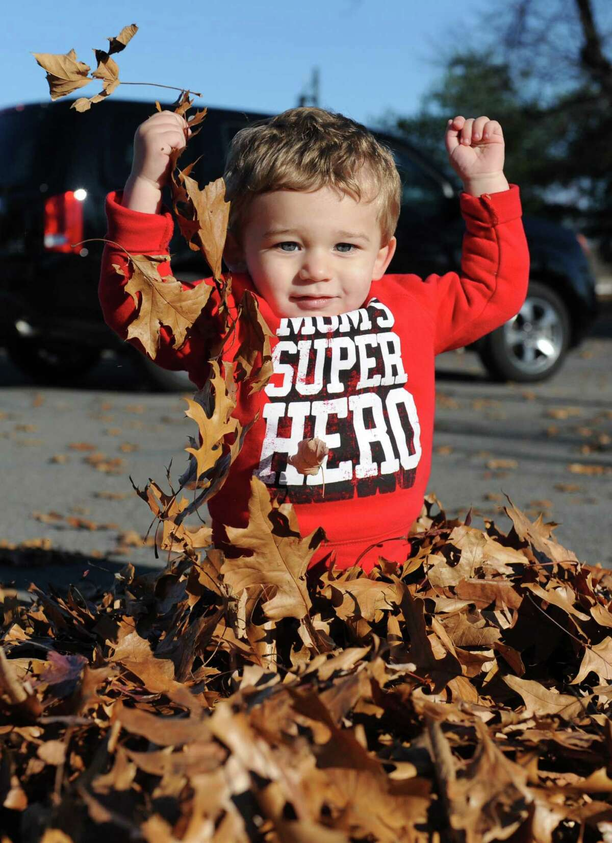 Hunter Lloyd of Schenectady, age 18 months, enjoys a mild day playing in leaves at The Crossings on Monday, Nov. 9, 2015, in Colonie, N.Y. (Lori Van Buren / Times Union))