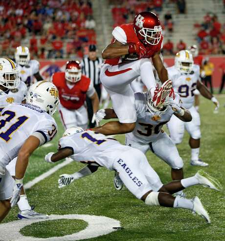 Houston's Chance Allen leaps over Tennessee Tech players for a first down during the first half of an NCAA college football game Saturday, Sept. 5, 2015, in Houston. (Craig H. Hartley/Houston Chronicle via AP) Photo: Craig Hartley, MBI / Houston Chronicle