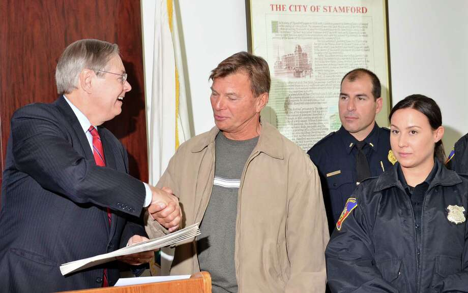 Mayor David Martin, left, issued a commendation Monday to Detective Bureau Sgt. Paul Guzda and his squad for the quick arrests in last Monday night's Lione Park murder. Standing to Guzday's left is Officer Nicole Petrenko, who spotted the vehicle carrying the three suspects who have been charged with the murder of of 43-year-old Maxine Gooden, a mother of five. Photo: Bernie Weiss / Contributed Photo / Stamford Advocate Contributed