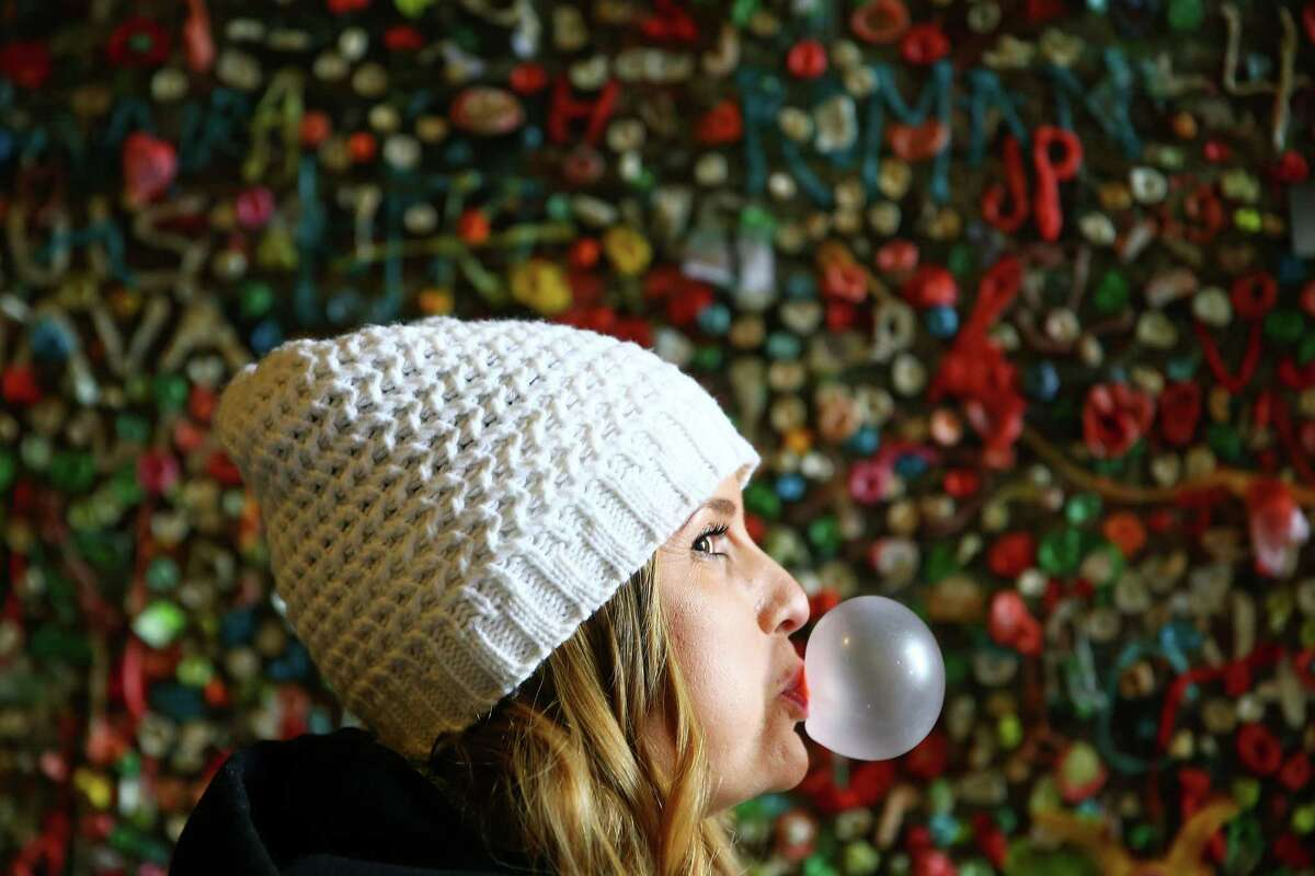 Heather Bowers blows a bubble while visiting the Post Alley Gum Wall the day before the wall will be completely cleaned for the first time in 20 years, Monday, Nov. 9, 2015. The alley was busy with people all day, coming to snap a photo and add to the wall before it's three-day cleaning.