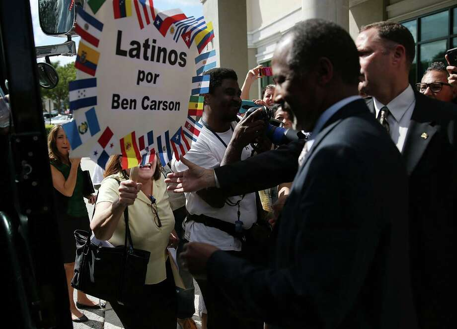 Latino voters gather around Republican presidential hoepfu; Ben Carson during a recent event in Florida. Some people are enamored of his outsider status. Not so one of our readers, who says Carson and Donald Trump contribute to voter alienation. Photo: Joe Raedle /Getty Images / 2015 Getty Images