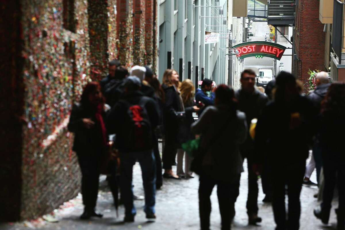 Post Alley was busy with visitors the day before the gum wall will be completely cleaned for the first time in 20 years, Monday, Nov. 9, 2015. People stopped in throughout the day, to snap a photo and add to the wall before it's three-day long cleaning.