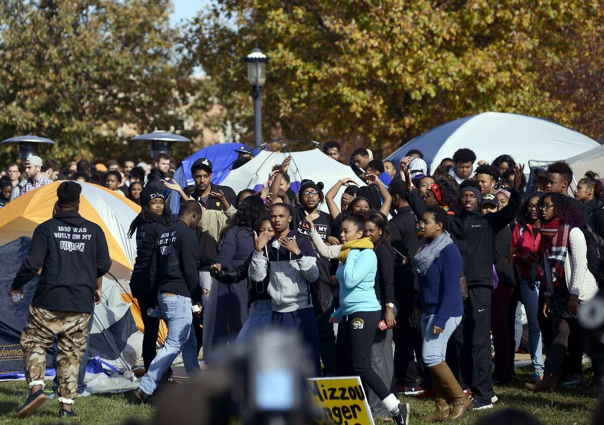 CORRECTS WITH NEW CAPTION - University of Missouri students celebrate as Jonathan Butler, center, waving, ended his hunger strike Monday, Nov. 9, 2015, now that University of Missouri System President Tim Wolfe has officially resigned, in Columbia, Mo. Wolfe has been under fire for his handling of race complaints that had threatened to upend the football season and moved Butler to go on a hunger strike. (Justin L. Stewart/Columbia Missourian via AP)