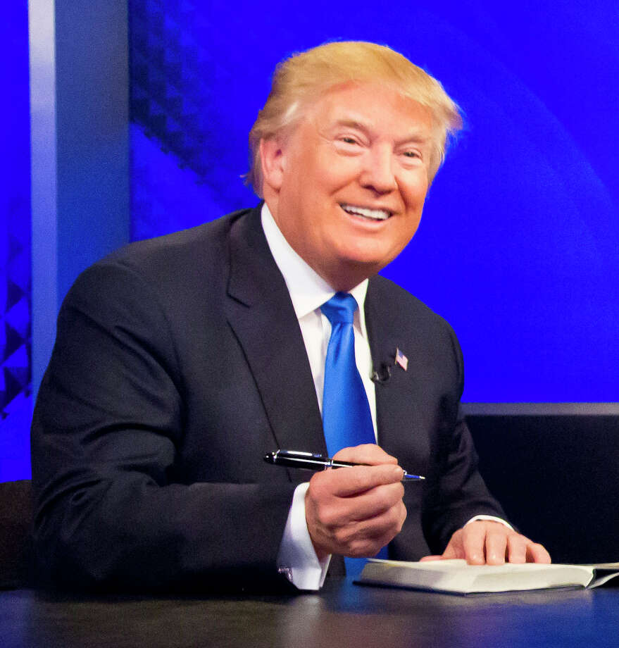 """Republican presidential candidate Donald Trump prepares to sign his book during his appearance on Fox's news talk show """"The O'Reilly Factor,"""" Friday, Nov. 6, 2015, in New York. (AP Photo/Bebeto Matthews) Photo: Bebeto Matthews, STF / AP"""