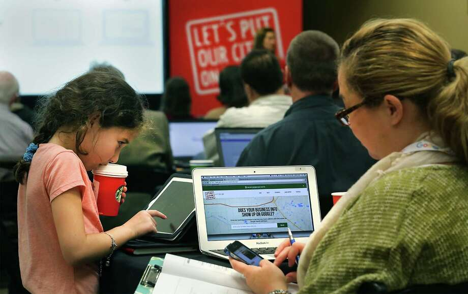 """Lillian Rosen, a 8-year-old daughter of Cynthia Rosen (right), works on her inscription Monday as her mom attends a """"Let's Put Our Cities on a Map"""" seminar, hosted by Google. Photo: Bob Owen /San Antonio Express-News / San Antonio Express-News"""