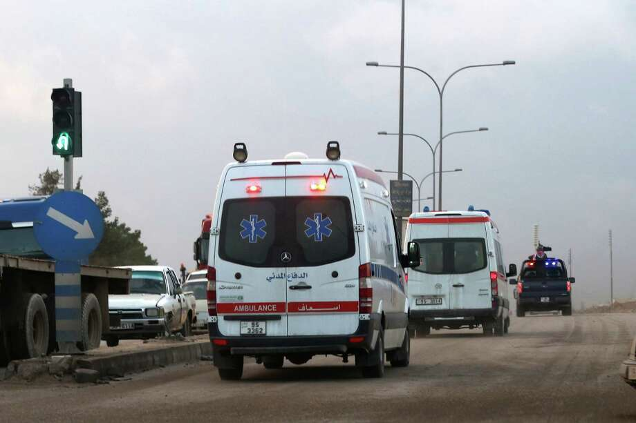 Ambulances leave the King Abdullah bin Al Hussein Training Center where a Jordanian policeman went on a shooting spree on Monday in Mwaqar on the outskirts of Amman, Jordan, November 9, 2015. The policeman opened fire Monday on foreign trainers at a police compound, killing two Americans, a South African and a Jordanian and wounding two Americans and three Jordanians, according to government spokesman Mohammed Momani. (AP Photo/Raad Adayleh) Photo: Raad Adayleh, STR / AP