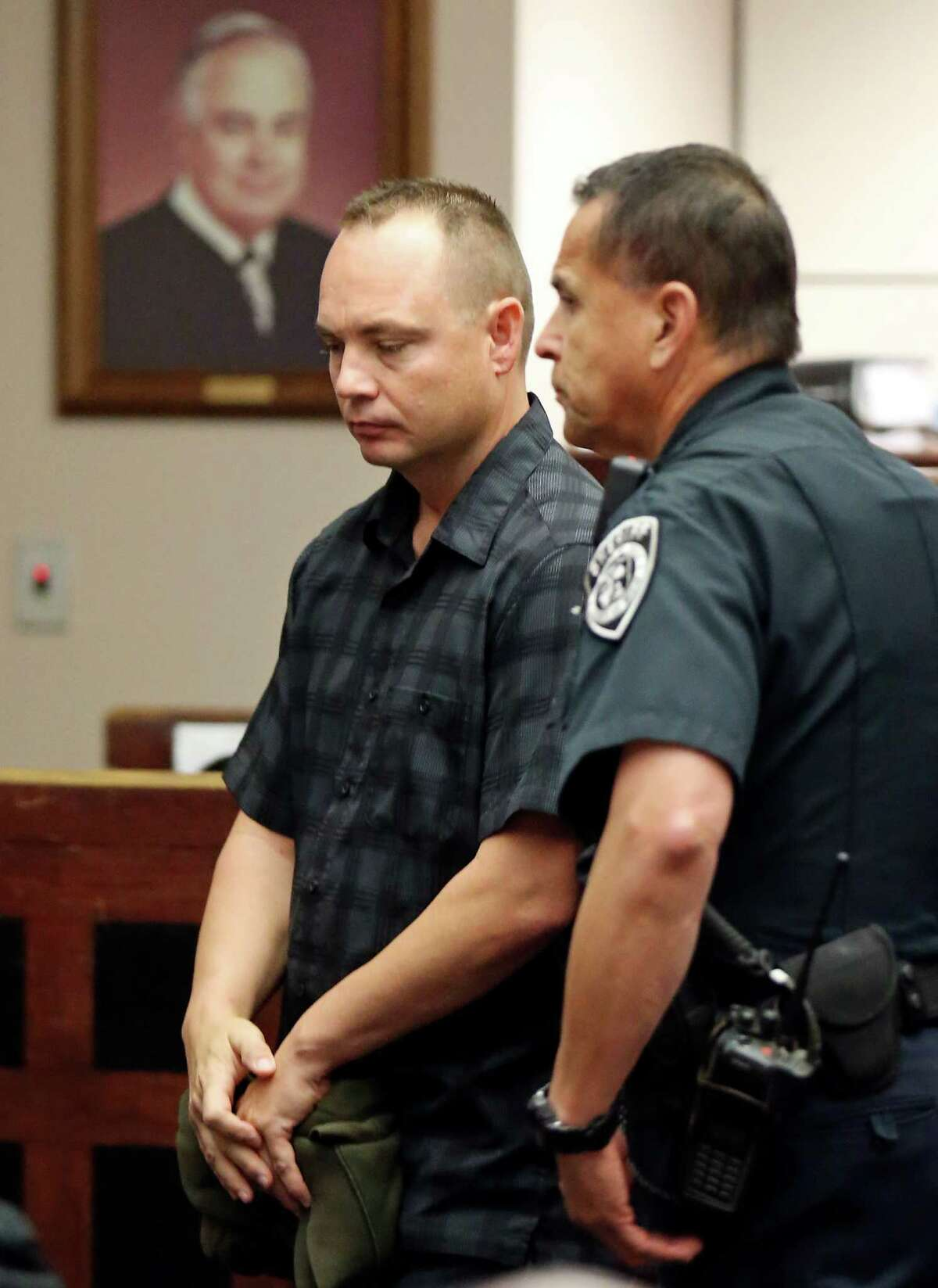 Former San Antonio police officer Jackie Len Neal (left) is escorted out of the 226th state District Court Monday Nov. 9, 2015 at the Cadena-Reeves Justice Center. Neal was accused of raping a woman in the back of his patrol SUV in 2013. He was fined and sentenced to 14 months in a state jail facility as part of a plea agreement. Neal pleaded no contest to improper sexual activity with a person in custody. As part of the deal, he was fined $5,000 and agreed to surrender his peace officer certification.