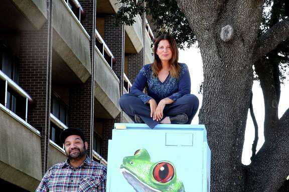 Studio owner Noah Quiles, left, and artist Anat Ronen check out the second mural Ronen created on a utility box in the Westchase District after the first was painted over by a graffiti abatement worker.