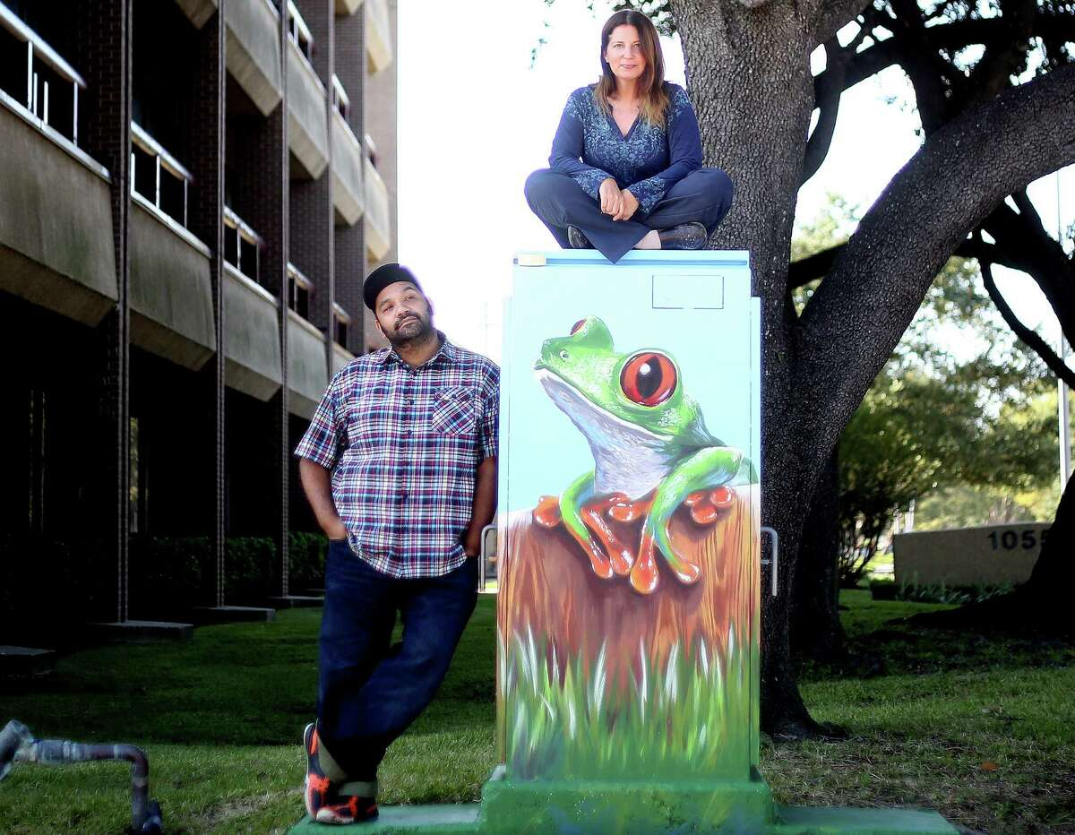 UP Art Studio owner Noah Quiles stands next to a piece by Anat Ronen, as the artist sits on it in Houston on Nov. 9, 2015. The muralist Anat Ronan and a mini mural she did in Houston that was mistakenly painted over 20 hours after she first painted it by Houston's anti-graffiti task forest. Monday, Nov. 9, 2015, in Houston.