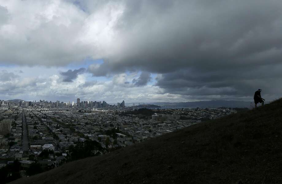 A man climbs Bernal Heights Hill on a cloudy day in San Francisco, Monday, Nov. 9, 2015. A storm system moving across California is bringing cool, wet weather to the low lands and snow in the Sierra Nevada mountains. Photo: Jeff Chiu, Associated Press