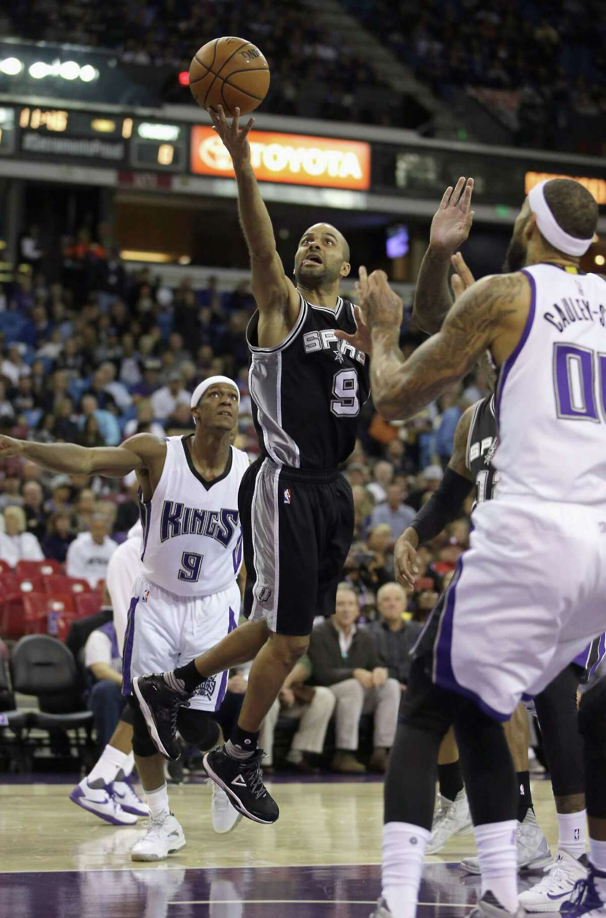 San Antonio Spurs guard Tony Parker, center, of France, goes the basket between Sacramento Kings' Rajon Rondo, left, and Willie Cauley-Stein, right, during the first quarter of an NBA basketball game in Sacramento, Calif., Monday, Nov. 9, 2015.(AP Photo/Rich Pedroncelli)