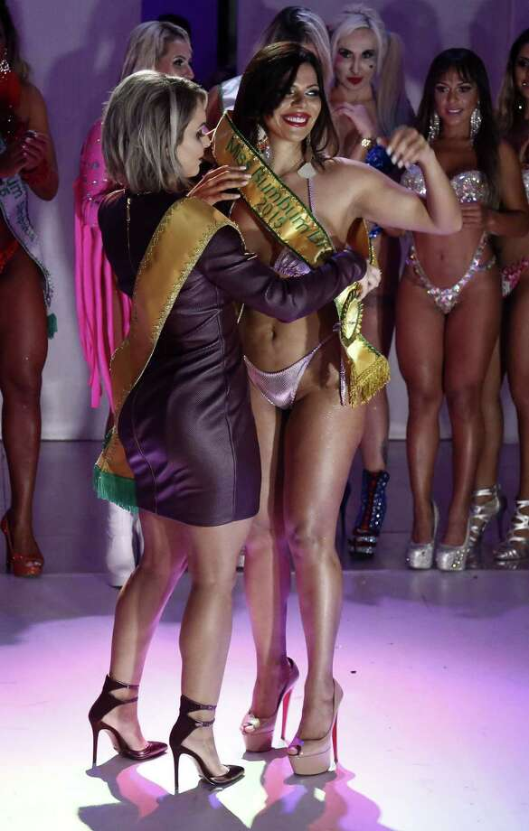 Suzi Cortez (R) from Distrito Federal receives the sash from Indianara Carvalho, Miss Bumbum 2014, after winning the Miss Bumbum Brazil 2015 pageant in Sao Paulo, Brazil on November 9, 2015. Photo: MIGUEL SCHINCARIOL, Getty Images / AFP
