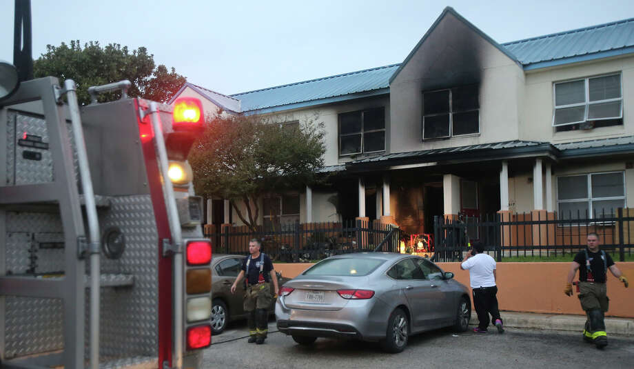 """San Antonio firefighters clear out debris Tuesday November 10, 2015 on the 900 block of Chihuahua after fire broke out in one of the apartments about 5:30 a.m.. Battalion chief Keith Crusius said four families are displaced because of the fire which was probably caused by lit candles. Crusius said the fire caused about $25,000 in damage to the structure and their were no injuries. Neighbor Eric Fontanez, whose family of four adults and two kids is bring displaced, said someone started banging on their door and yelled for them to get out. """"I've never seen so much fire at one time. I'm just glad we're all alive,"""" Fontanez said. Photo: John Davenport, San Antonio Express-News / ©San Antonio Express-News/John Davenport"""