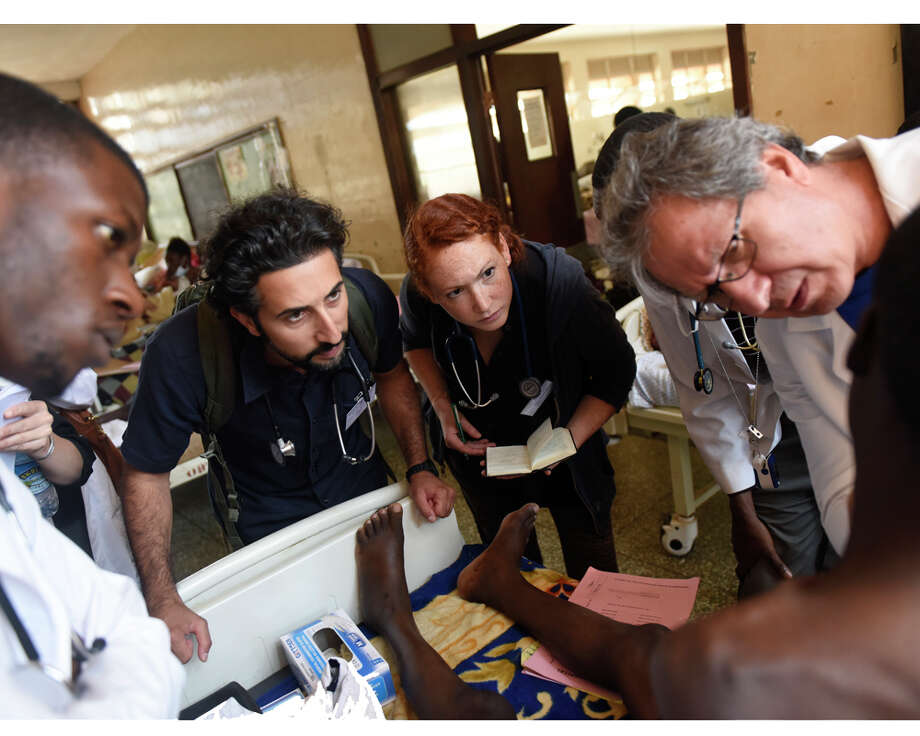 From left, Dr. Brian Beesiga, Dr. Sohi Ashraf, of Norwalk, Conn., University of Vermont first-year medical student Mary-Kate LoPiccolo, of Newtown, Conn., and Danbury Hospital Global Health Department Director Dr. Majid Sadigh examine a patient during clinical rounds at Mulago Hospital in the capital city of Kampala, Uganda Saturday, July 25, 2015. Photo: Tyler Sizemore / Hearst Connecticut Media / Greenwich Time
