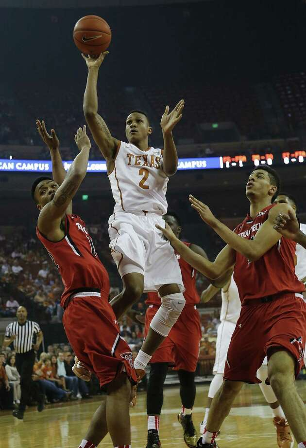 AUSTIN, TX - FEBRUARY 14: Demarcus Holland #2 of the Texas Longhorns shoots between Robert Turner #14 and Zach Smith #11 of the Texas Tech Red Raiders at the Frank Erwin Center on February 14, 2015 in Austin, Texas. (Photo by Chris Covatta/Getty Images) Photo: Chris Covatta, Stringer / 2015 Getty Images