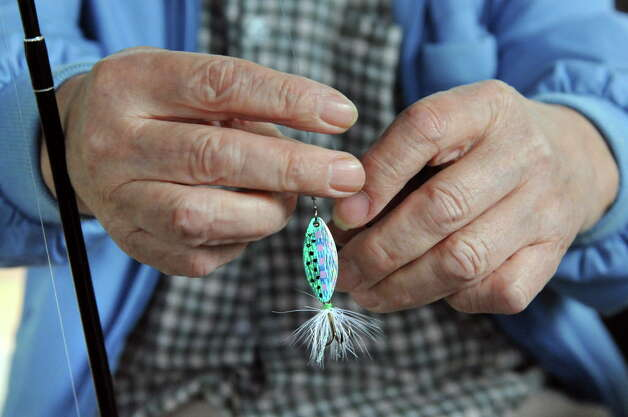 Ted Yoshinari of the Colonie Seniors ties a lure on his line during a Department of Environmental Conservation Free Sport Fishing Clinic on Tuesday, May 19, 2015, at Six Mile Waterworks in Albany, N.Y. The clinics, which are held across the state, allow would-be-fishing enthusiasts the chance to receive instruction and try the sport without a license. For more information visit www.dec.ny.gov. (Cindy Schultz / Times Union) Photo: Cindy Schultz / 00031852A