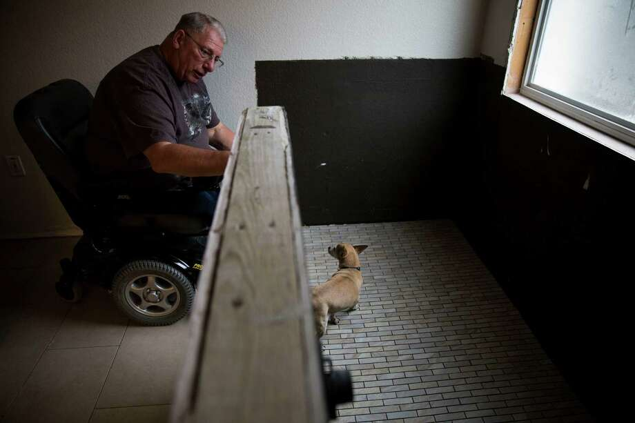 Hendershot, who was wounded in 1967 in a battle with North Vietnamese soldiers, and his dog Emmett check out the renovation work on the shower. Photo: Carolyn Van Houten /Carolyn Van Houten / 2015 San Antonio Express-News