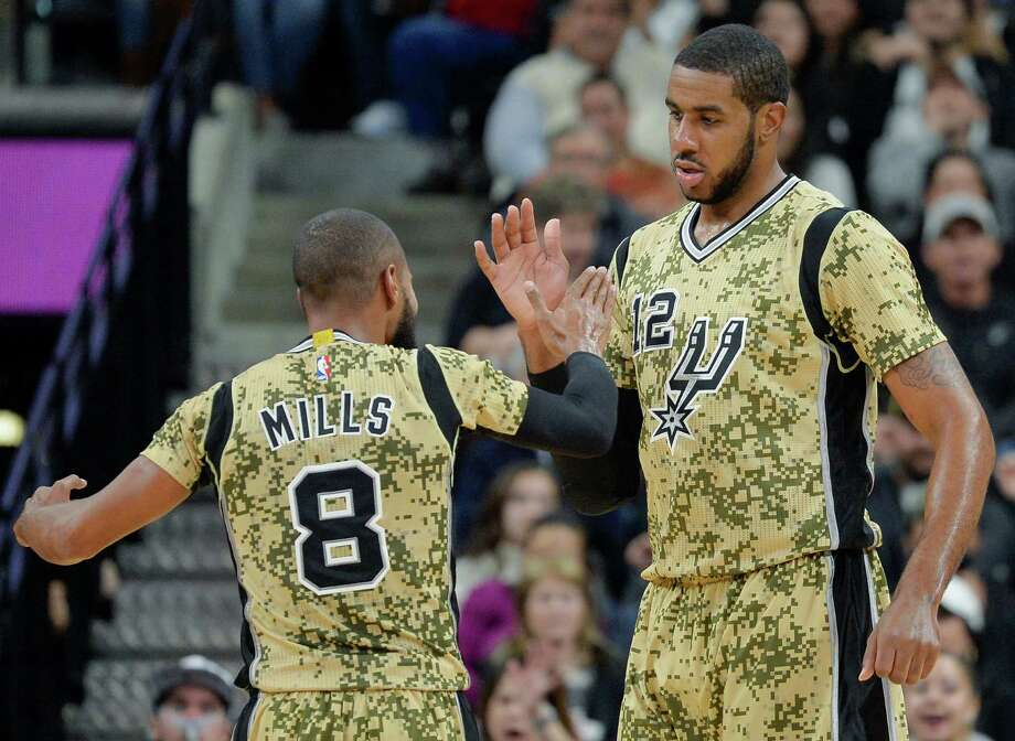 Spurs forward LaMarcus Aldridge (right) celebrates a basket with guard Patty Mills during the first half against the Charlotte Hornets on Nov. 7, 2015, in San Antonio. Photo: Darren Abate /Associated Press / FR115 AP