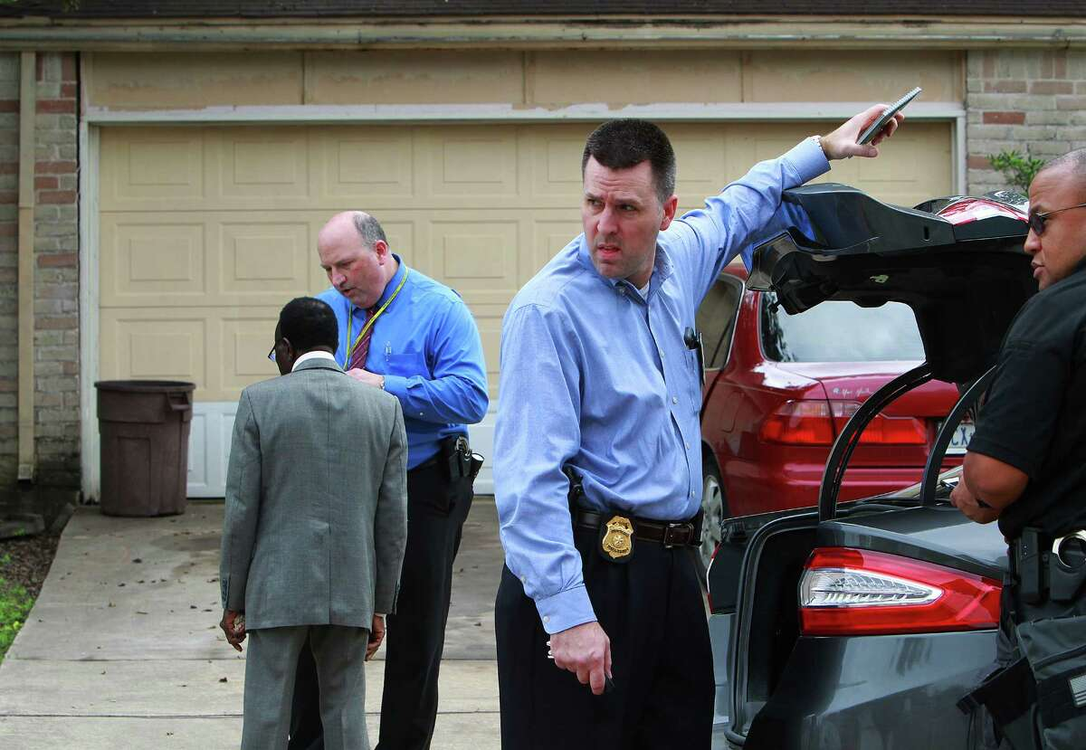 Innocent Onyeri (left), whose son Chimene Onyeri is being held by police for questioning in the attack on state District Judge Julie Kocurek, talks to Austin Police Department detective Derek Israel (center, in blue) while police search the residence, Tuesday, Nov. 10, 2015, in Houston.