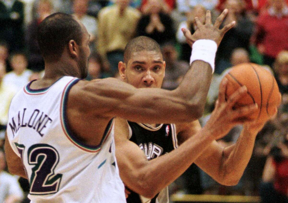 Utah Jazz forward Karl Malone (32) pressures San Antonio Spurs forward Tim Duncan into making a last second shot that could have tied the game in the fourth quarter Feb. 6, 2000, in Salt Lake City. Duncan missed. The Jazz beat the Spurs 93-90.
