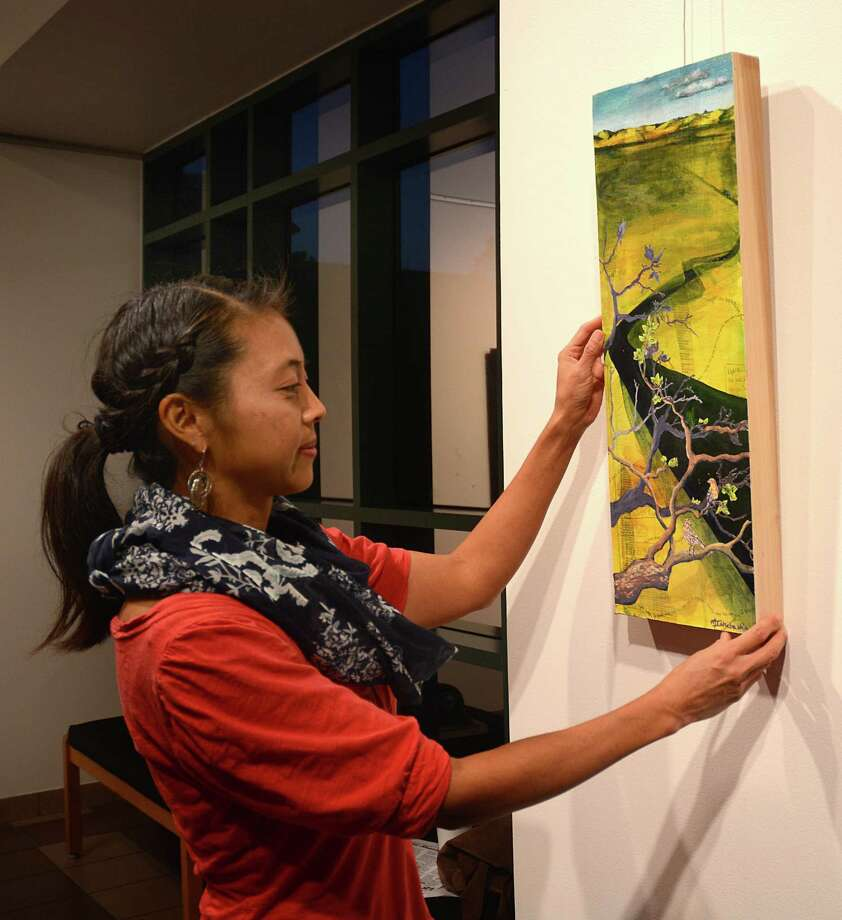 "Oak Ridge High School art instructor Midori Ishibashi-Wall straightens her mixed media art piece ""What's Meant to be, Confused Series"" during the exhibit opening night at Lone Star College-Montgomery's Mary Matteson-Parrish Art Gallery. LSC-M art department is hosting the exhibit showcasing the talent of area  local high school art teachers Photograph by David Hopper Photo: David Hopper, Freelance / freelance"