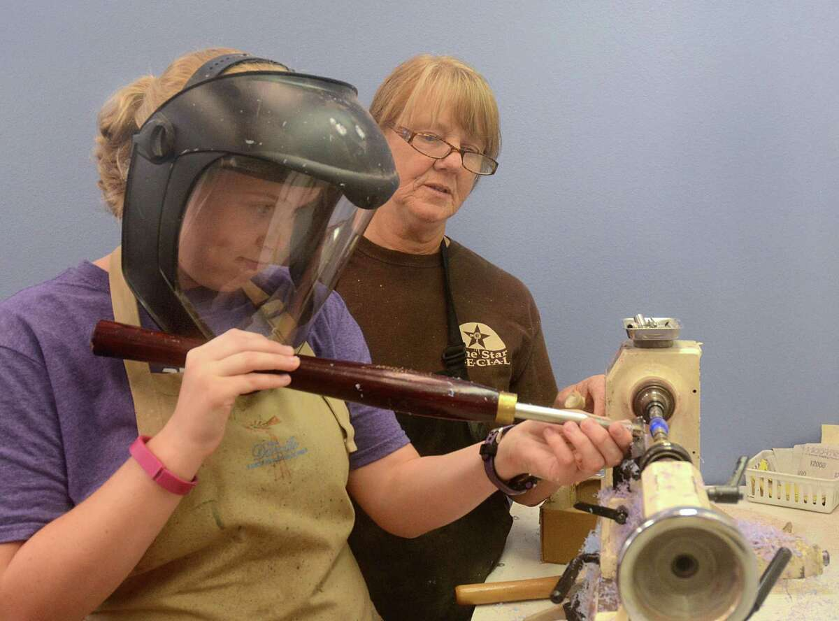 Wood working instructor Sherry Franklin, of Willis, watches as Rebecca Penny, of The Woodlands, uses a lathe to turn a ink pen block at New Danville, 10951 Shepard Hill Road in Willis. New Danville is a community where people with developmental disabilities can learn to work and live in a community. Photograph by David Hopper