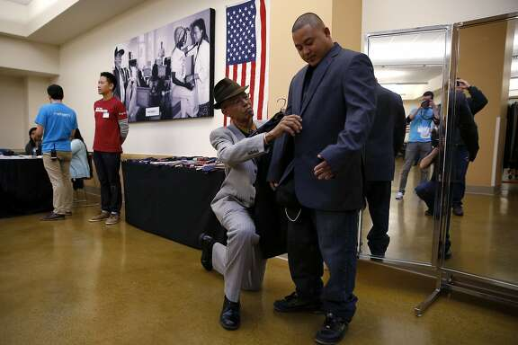 Del Seymour adjusts Mixon Matignas' new jacket during an event to help veterans at the St. Anthony Foundation in San Francisco, California, on Tuesday, Nov. 10, 2015.