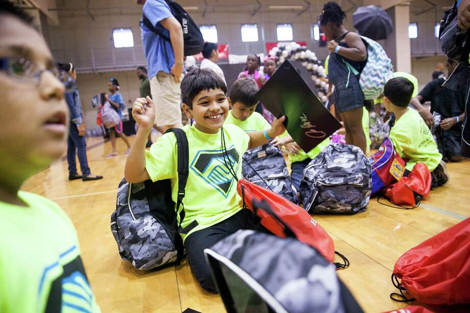 Jesse Gutierrez, 9, cheers after receiving his backpack during this year's back-to-school bash, hosted by Spurs forward LaMarcus Aldridge and H-E-B held for 200 students from 3rd Ð 5th grades and their families on Sat. Aug. 15, 2015 at the George Gervin Academy. Students received a backpack filled with a yearÕs worth of school supplies. / Julysa Sosa For the San Antonio Express-News