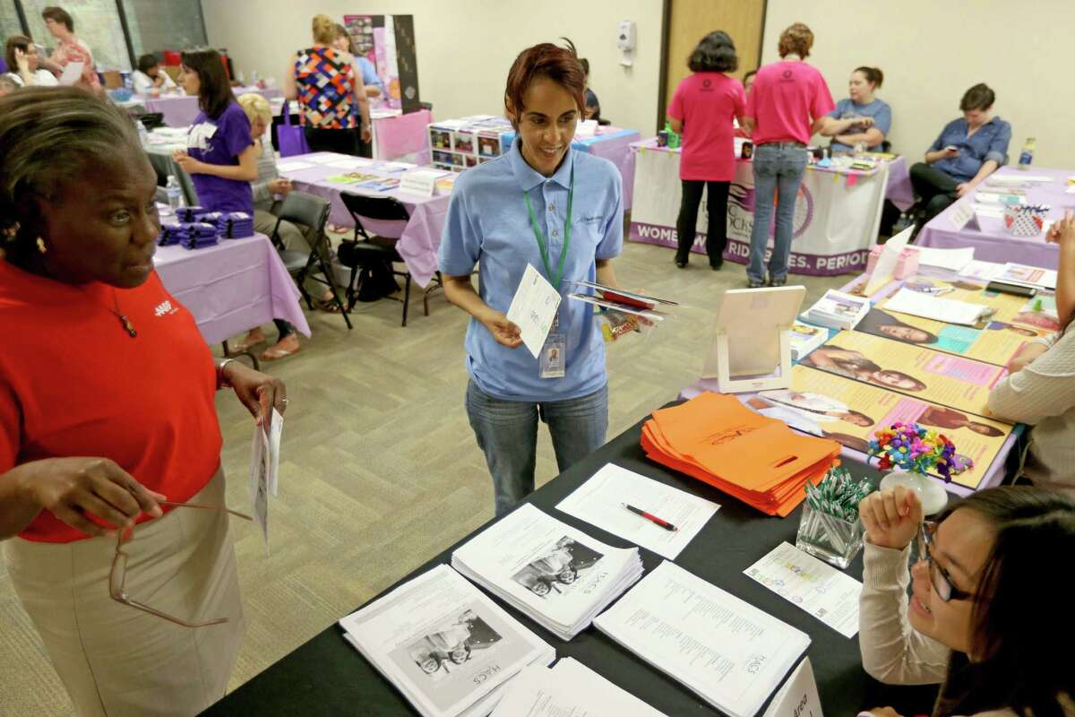 Roza Hassen, center, in person assister with Houston North Enrollment Assistance Center, takes a break from handing out information about the Affordable Care Act federal marketplace insurance benefits, to browse the booths at the the Houston Lesbian Health Initiative event held at the Houston Area Community Services Saturday, Nov. 7, 2015, in Houston, Texas. ( Gary Coronado / Houston Chronicle )