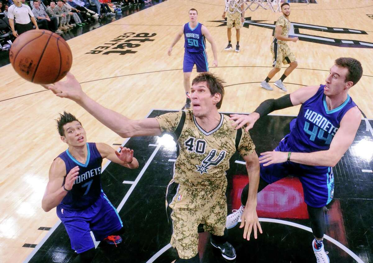 San Antonio Spurs' Boban Marjanovic grabs for a rebound between Charlotte Hornets' Jeremy Lin (left) and Frank Kaminsky during their game Saturday Nov. 7, 2015 at the AT&T Center. The Spurs won 114-94.