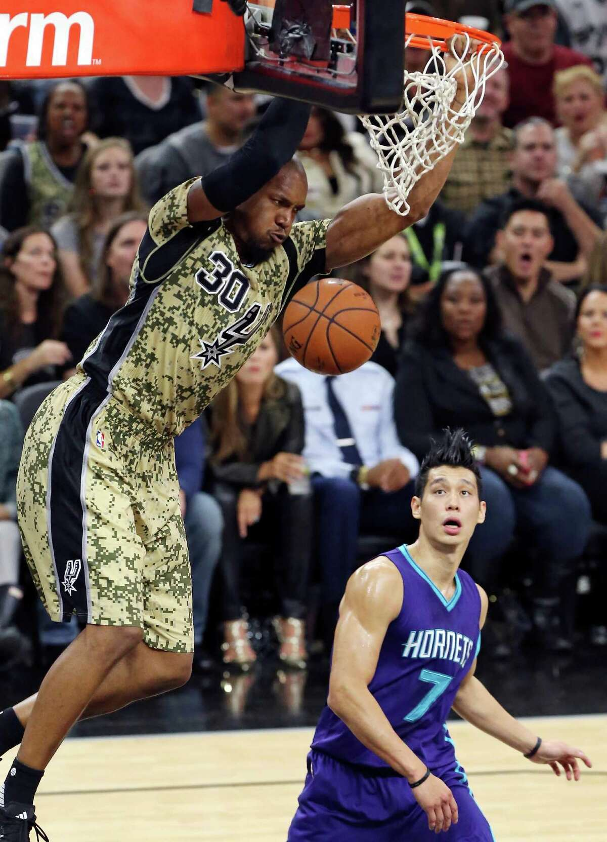 San Antonio Spurs' David West dunks as Charlotte Hornets' Jeremy Lin looks on during second half action against the Charlotte Hornets Saturday Nov. 7, 2015 at the AT&T Center. The Spurs won 114-94.