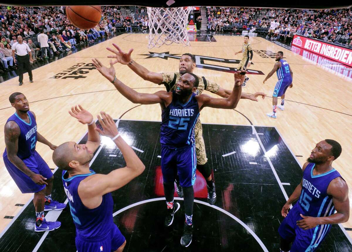 San Antonio Spurs' Tim Duncan and Charlotte Hornets' Al Jefferson grab for a rebound as Charlotte Hornets' Marvin Williams (from left), Nicolas Batum, and Kemba Walker look on during their game Saturday Nov. 7, 2015 at the AT&T Center. The Spurs won 114-94.