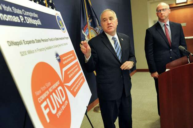 Comptroller Thomas P. DiNapoli, center, and Dave Helgerson, managing director of Hamilton Lane, unveil a new program to offer credit for NY-based businesses on Tuesday, Nov. 10, 2015, at the New York State Comptrollers Office in Albany, N.Y. (Cindy Schultz / Times Union) Photo: Cindy Schultz / 00034169A