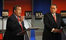 Chris Christie, right, makes a point as Mike Huckabee listens during Republican presidential debate at Milwaukee Theatre, Tuesday, Nov. 10, 2015, in Milwaukee. (AP Photo/Morry Gash)