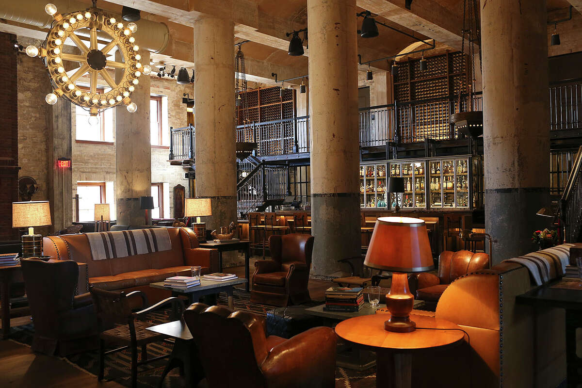 The Sternewirth bar at the Hotel Emma includes a 25-foot ceiling, repurposed cast-iron fermentation tanks that now serve as lounge seating and a repurposed bottle labeler made into a chandelier.
