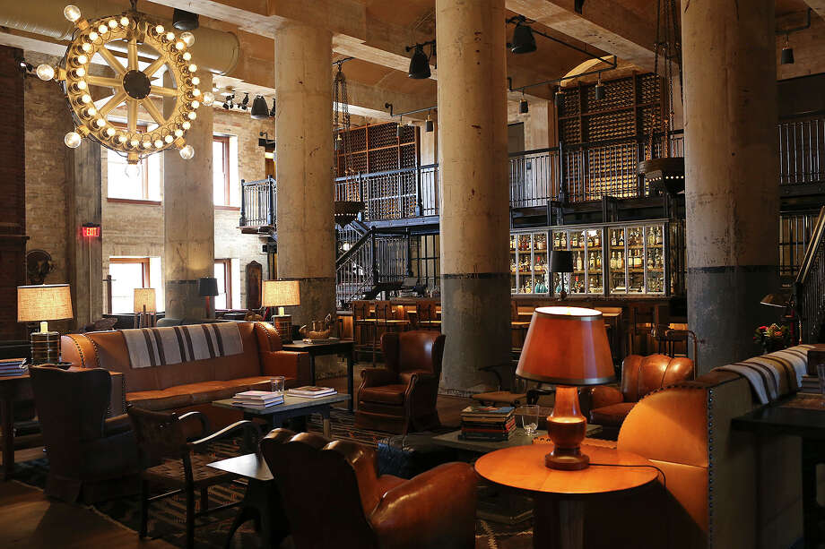 The Sternewirth bar at the Hotel Emma includes a 25-foot ceiling, repurposed cast-iron fermentation tanks that now serve as lounge seating and a repurposed bottle labeler made into a chandelier. Photo: Jerry Lara /San Antonio Express-News / © 2015 San Antonio Express-News