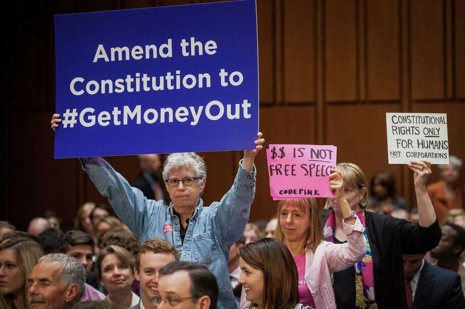 Code Pink activists hold up signs in support of a proposed constitutional amendment on campaign finance during a Senate Judiciary Committee hearing in Washington, D.C., U.S., on June 3, 2014 (Pete Marovich/Bloomberg) Photo: Pete Marovich / © 2014 Bloomberg Finance LP