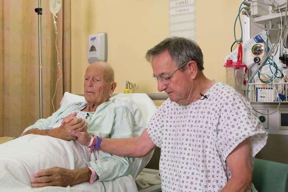 "Vietnam veterans Henry ""Bill"" Warner, left, and John Middaugh clasp hands prior to their surgeries Nov. 5 at NewYork-Presbyterian/Weill Cornell Medical Center in New York. Photo: Mark Lennihan, STF / AP"