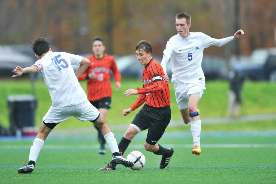 Ridgefield senior Matthew Wilson, center, weaves between Darien's Andrew Mathew (15) and Sam Pfrommer (5) during Tuesday's Class LL tournament game at Darien High School. Photo: Michael Cummo / Hearst Connecticut Media / Stamford Advocate