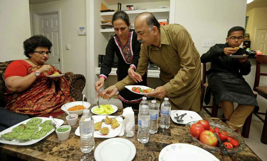 "Kavita Vachaknavee, from left, enjoys food Monday in the family home of Padma Sharma, with Sharma's husband, Kishwar, and their son, Pratik, 15, right, during Diwali, the Hindu ""Festival of Lights."" Photo: Melissa Phillip, Staff / © 2015 Houston Chronicle"